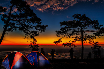 silhouette of tourists wake up each morning watching the sun rise over the mountains, near the tent point