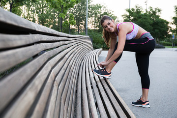 Pretty fit woman tightening laces on shoes while working out in park.