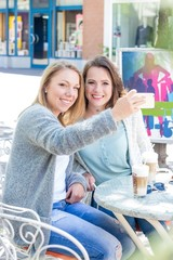 Two friends walk through the city and drink Cappuccino. Two young women sitting in the Cafe. Communication Warm spring. Summer.