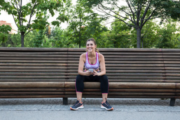Pretty fit young woman on park bench.