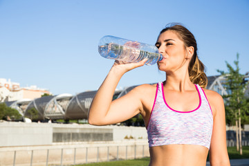 Young woman in sportswear drinking water and looking away on urban background.