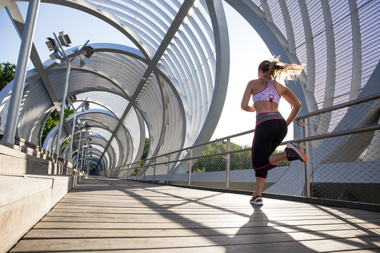 Anonymous sportswoman in motion of running in modern urban passage in summer.
