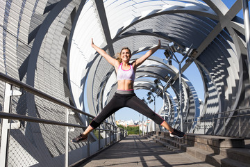 Young sportive girl in sportswear jumping high above ground posing happily on urban background.