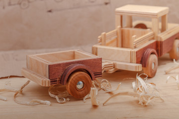 A wooden car with a trailer on a table with sawdust