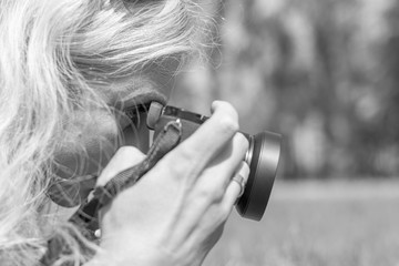 Professional woman photographer taking outdoor with prime lens, during a sunny day in the spring park. Black and white. Shallow depth of field.