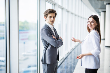 two young businessman and business woman are standing in modern office with panoramic windows.