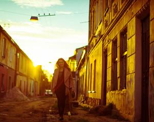 Pretty lady in beige jacket walks on the autumn street