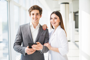 Two smiling elegant business people man in formal suit and woman in jacket and dress looking at something on digital tablet in office interior near window