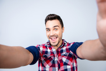 Funky mood of an excited geek young man in casual wear. He is making selfie shot on camera, standing on a pure background, fooling around