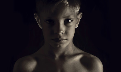 Young athletic boy on a dark background
