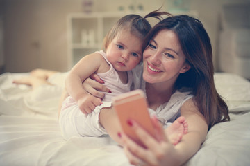 Mother with her little baby having fun in the bed. Mother making self-picture with her cute little baby in the bed.