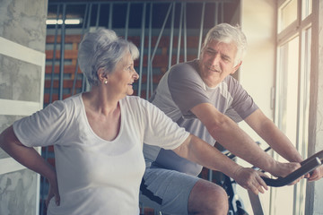 Two senior people at the gym. Senior man sitting on the elliptical machine and having conversation with senior woman.