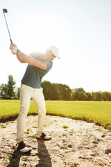Golfer about to hit ball out of a sand bunker