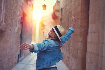 Happy woman walking on mediterreanen street in sunset