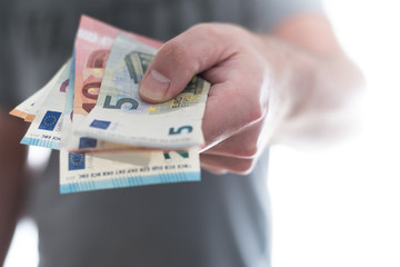hand of male person handing over a couple of different euro bills