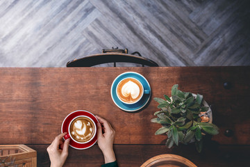 Top view of Decorating and Interior Design for Coffee Shop, Cup of hot Latte in Woman hand Lay on Wooden Table