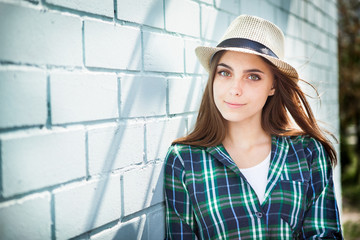 Beautiful teenage girl in hat near blue wall