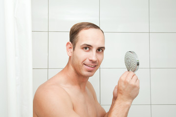 man in the bathroom adjusts the water pressure in the shower