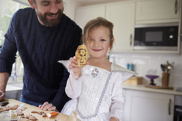 Father And Daughter Decorating Halloween Cookies Together