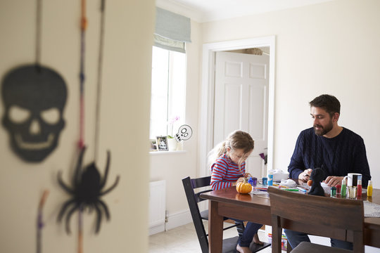 Father And Daughter Decorating Halloween Masks Together
