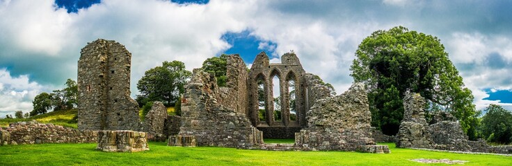 Inch Abbey with a blue sky in Northern Ireland. Monastery ruins in Downpatrick. Co. Down. Travel by car in summer.