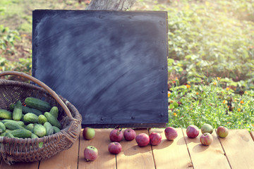 vegetables and fruits/ Old wicker basket with a cucumbers  crop on a table with apples and a board for graffiti