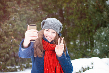 Young beautiful woman taking selfie photo in winter snow park