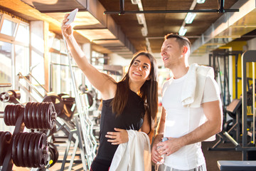Smiling athletic friends taking selfie at gym.