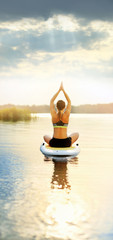 Picture of a woman meditating on paddle board early morning