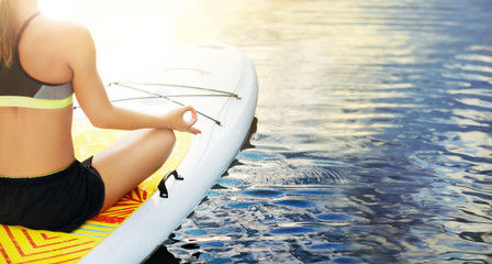Wide view picture of woman sitting on paddle board holding fingers in  mudra gesture