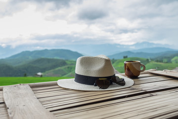 Hats, sunglasses, a coffee mug that is placed on a wooden balcony. In the bright morning air