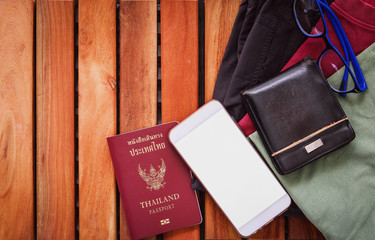 Top view clothing and pants  traveler's passport ,wallet, glasses, smart phone devices, on a wooden floor in the ready to travel.