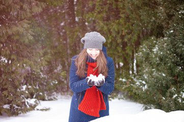Portrait of young woman playing with snow, outdoors. Smiling girl walking in a winter park  and having fun on a cold sunny day.