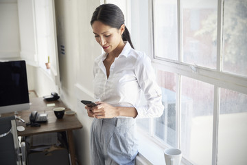 Young businesswoman using smartphone in the office