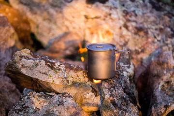A mug near a camping fire on a hike trip