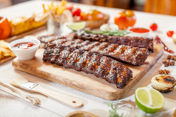 Spicy hot grilled spare ribs from a summer BBQ served with chips, corn and fresh tomatoes on an old wooden cutting board