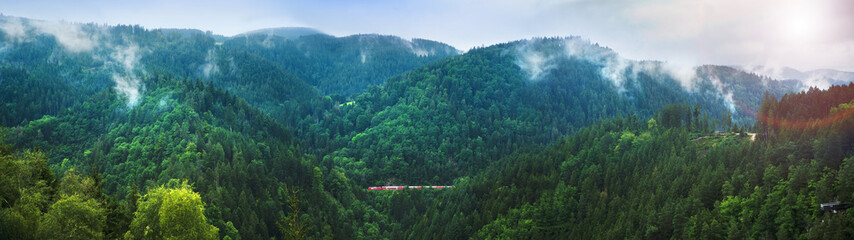 Panorama of small train in Black Forest covered in soft clouds