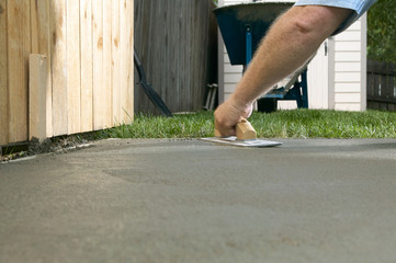 Person finishing wet cement with concrete screed