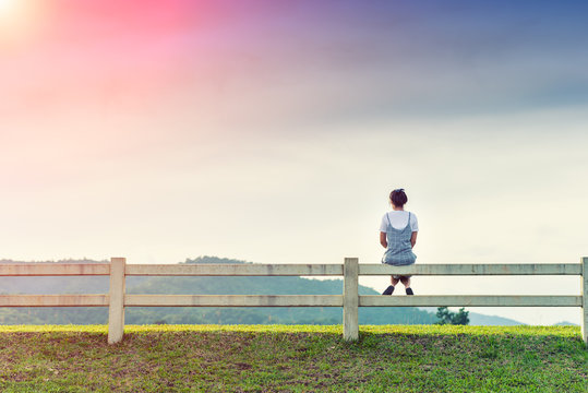 Young woman sitting on fence and sunlight