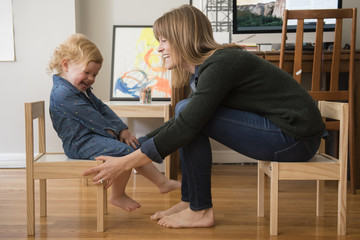 Caucasian mother and daughter sitting on small chairs in home office