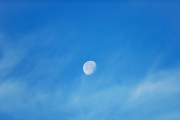 Moon with light clouds in its waning gibbous phase during daytime
