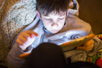 Mixed Race boy using digital tablet at night
