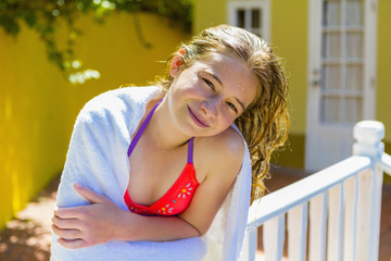 Wet Caucasian girl leaning on railing