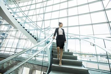 Pensive Mixed Race businesswoman descending staircase