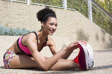 Mixed Race woman stretching legs on path