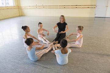 Teacher and students sitting on floor in ballet studio