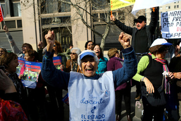 Retired teachers shut slogans in front of the government building during a teachers' strike in Santiago,