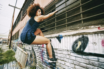 Hispanic woman climbing on bar on graffiti wall