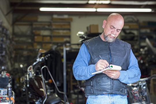 Caucasian man near motorcycle writing on notepad