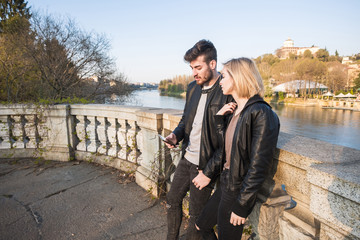 Caucasian couple texting on cell phone near river